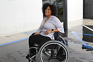 an African American woman in a wheelchair posing for the camera, smiling